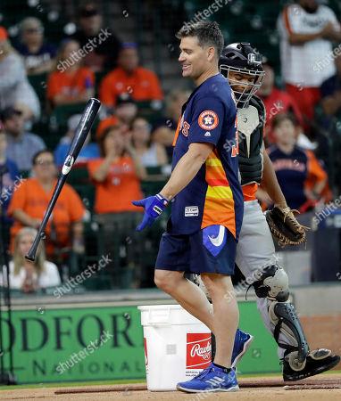 Former Houston Astros outfielder Luke Scott flips his bat after competing in a legends weekend home run derby, in Houston. Scott won the event