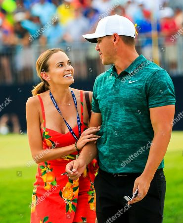Brooks Koepka of the US (R) walks with his girlfriend Jena Sims (L) as he leaves the 18th green to win the 100th PGA Championship golf tournament at Bellerive Country Club in St. Louis, Missouri, USA, 12 August 2018.