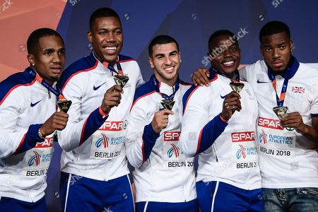 Chijindu Ujah (L), Zharnel Hughes (2-L), Adam Gemili (C), Harry Aikines-Aryeetey (2-R) and an unknown person (R) of Britain pose during the awarding ceremony of the men's 4x100m Relay at the Athletics 2018 European Championships, Berlin, Germany, 13 August 2018.