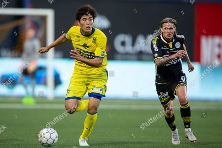 Takehiro Tomiyasu and Ari Freyr Skulason fight for the ball