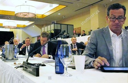 Stock Image of Charlie Baker, Philippe Couillard, Phil Scott, Brian Gallant, Dannel P Malloy. From left at table, Massachusetts Gov. Charlie Baker (partially obscured), Quebec Premier Philippe Couillard, Vermont Gov. Phil Scott, New Brunswick Premier Brian Gallant and Connecticut Gov. Dannel P Malloy attend the Conference of New England Governors and Eastern Canadian Premiers, in Stowe, Vt