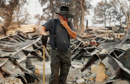 Ed Bledsoe tries to hold back tears as he searches through what remains of his home, in Redding, Calif. Bledsoe's wife, Melody, great-grandson James Roberts and great-granddaughter Emily Roberts were killed at the home in the Carr Fire