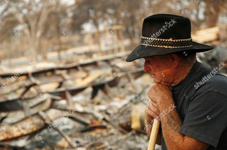 Stock Picture of Ed Bledsoe rests as he searches through what remains of his home, in Redding, Calif. Bledsoe's wife, Melody, great-grandson James Roberts and great-granddaughter Emily Roberts were killed at the home in the Carr Fire