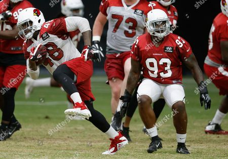 Arizona Cardinals running back Derrick Coleman (48) changes direction as he tries to elude defensive end Arthur Moats (93) during an NFL football practice, in Glendale, Ariz