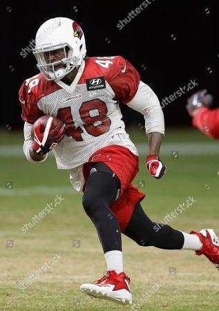 Arizona Cardinals fullback Derrick Coleman runs with the ball during an NFL football practice, in Glendale, Ariz
