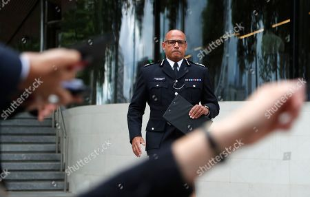 Assistant Commissioner Neil Basu arrives to speak to the media outside New Scotland Yard in London,. Authorities said in a statement Tuesday that a man in his 20s was arrested on suspicion of terrorist offenses after a silver Ford Fiesta collided with a number of cyclists and pedestrians before crashing into the barriers during the morning rush hour