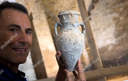 Uri Geller owner of Uri Geller Museum and an illusionist and television personality show a water or oil jug found at a 'Masbena' in Arabic or a soap manufacturing factory from olive oil dated to the 19th Century from the Ottoman Empire period, in the Old City of Jaffa, outskirts of the Israeli coastal city of Tel Aviv, 14 August 2018. According to the Israel Antiquities Authority Jaffa expert, this previously unknown factory, is the second of its kind to have been discovered in Jaffa. The site was well preserved and included troughs for mixing raw materials for the soap, a large cauldron, a hearth, water cisterns and underground vaults that were used for storage. The production of soap from olive oil was sold locally, while a large share was destined for export to regions within the Ottoman Empire, mainly for the Egyptian market.