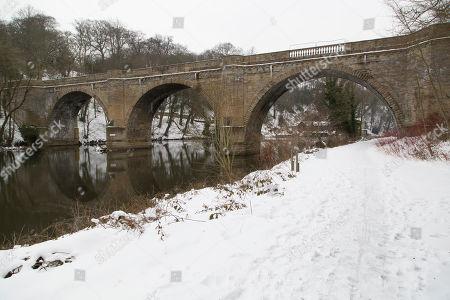 Prebends Bridge on a snowy day in Durham City, England. The stone bridge crosses the River Wear.