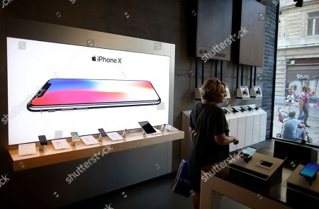 A woman checks mobile phones in front of a Apple iphone X picture at a shop in Istanbul, Turkey, 14 August 2018. Turkish President Erdogan says Turkey will boycott US electronic goods, including Apple's iPhone and if they have iPhone, there is Samsung and Vestel Venus on the other side. The Turkish central bank on 13 August 2018 said it was closely monitoring the lira's performance and seek counter-measures. The Turkish lira hit a new record low against the US dollar within the scope of an escalating feud with the USA.