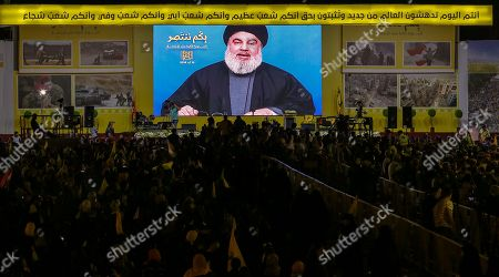 Hezbollah supporters wave Hezbollah flags as they listen to the speech of Hezbollah leader Hassan Nasrallah via a giant screen   in  southern suburb of Beirut, Lebanon, 14 August 2018.  Hassan Nasrallah, the Hezbollah leader, spoke to thousands of supporters gathered at a rally to mark the 12th anniversary of the end of the 2006 July War between Hezbollah and Israel. Supporters at the rally watched his speech on giant screens as it was broadcast from a secret location.