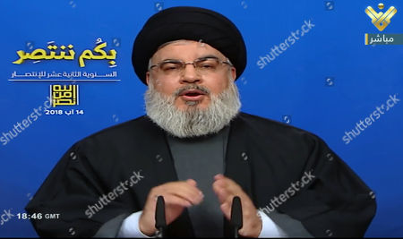 A video grab from the Hezbollah-run al-Manar television station shows Lebanese Hezbollah chief Hassan Nasrallah delivering a televised speech from an undisclosed location on 14 August 2018. Hassan Nasrallah, the Hezbollah leader, spoke to thousands of supporters gathered at a rally to mark the 12th anniversary of the end of the 2006 July War between Hezbollah and Israel. Supporters at the rally watched his speech on giant screens as it was broadcast from a secret location.