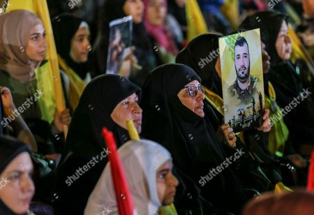 Women  supporters 0f  Hezbollah carry pictures of their martyrs sons  as they listen to the speech of Hezbollah leader Hassan Nasrallah via a giant screen  in  southern suburb of Beirut, Lebanon, 14 August 2018.  Hassan Nasrallah, the Hezbollah leader, spoke to thousands of supporters gathered at a rally to mark the 12th anniversary of the end of the 2006 July War between Hezbollah and Israel, where they watched his speech on giant screens as it was broadcast from a secret location.