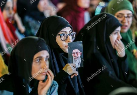 Hezbollah supporters carry pictures of Hezbollah leader Hassan Nasrallah as they listen to the speech via a giant screen  in  southern suburb of Beirut, Lebanon, 14 August 2018.  Hassan Nasrallah, the Hezbollah leader, spoke to thousands of supporters gathered at a rally to mark the 12th anniversary of the end of the 2006 July War between Hezbollah and Israel, where they watched his speech on giant screens as it was broadcast from a secret location.
