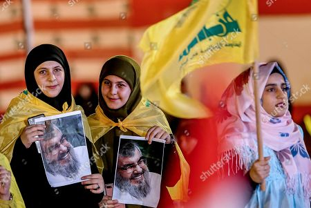 Hezbollah supporters wave Hezbollah flag carry pictures of Hezbollah leader Hassan Nasrallah as they listen to the speech via a giant screen  in  southern suburb of Beirut, Lebanon, 14 August 2018.  Hassan Nasrallah, the Hezbollah leader, spoke to thousands of supporters gathered at a rally to mark the 12th anniversary of the end of the 2006 July War between Hezbollah and Israel, where they watched his speech on giant screens as it was broadcast from a secret location.