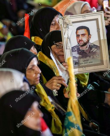 Hezbollah supporter woman carry the picture of her martyr son as she  listen to the speech of Hezbollah leader Hassan Nasrallah via a giant screen in  southern suburb of Beirut, Lebanon, 14 August 2018. Hassan Nasrallah, the Hezbollah leader, spoke to thousands of supporters gathered at a rally to mark the 12th anniversary of the end of the 2006 July War between Hezbollah and Israel, where they watched his speech on giant screens as it was broadcast from a secret location.