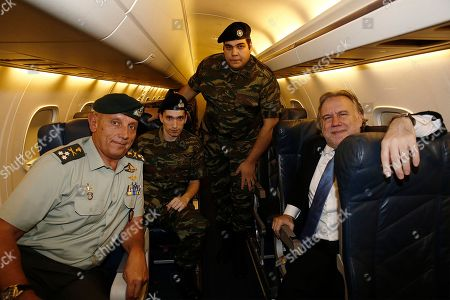 Greek lieutenant Aggelos Mitretodis (2-L) and noncommissioned officer Dimitros Kouklatzis (2-R) pose with the Greek Alternate Minister of Foreign Affairs George Katrougalos (R) and Deputy Chief of the HNDGS Lieutenant General Konstantinos Floros (R) during the flight from Turkey to Thessaloniki Airport in Thessaloniki, Greece, 15 August 2018. A Turkish court ruled on 14 August the release of two Greek officers that had been detained since March for entering a military zone in Turkey on the border with Greece. The Edirne court did not impose any restrictive travel measures on the two men, which means they will be allowed to return to Greece. During the court hearing, the two Greek officers and their lawyers sought their immediate release on the grounds that an examination of the digital devices held by the two men failed provide show any signs espionage. The two Greek officers told the court they had entered Turkey by mistake, following footprints which they had located on the Greek side. The judge agreed there is no evidence of espionage, deciding they will only face charges of illegally entering a military zone. Greek Prime Minister Alexis Tsipras said 'the release of the two Greek military officers is an act of justice, which will help to strengthen friendship, good neighborly ties and stability in the region.' 'I would like to congratulate and thank our two officers and their families for their courage, patience and confidence in the efforts of all of us, which were ultimately justified,' he added.