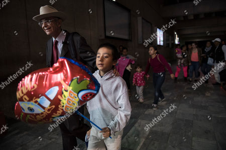 Stock Picture of Anthony David Tovar Ortiz, Ricardo de Anda. Anthony David Tovar Ortiz, center, is accompanied by attorney Ricardo de Anda after arriving to La Aurora airport in Guatemala City, . The 8-year-old stayed in a shelter for migrant children in Houston after his mother Elsa Ortiz Enriquez was deported in June 2018 under President Donald Trump administration's zero tolerance policy