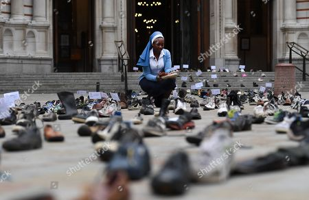 Sister Clara from Catholic charity CAFOD walks amongst shoes outside Westminster Cathedral in London, Britain, 15 August 2018.  Hundreds of shoes left outside Westminster Cathedral in London are part of a campaign which was launched by Pope Francis and has been supported by tens of thousands of people across the UK. The campaign, led by Catholic charities CAFOD and the Catholic Social Action Network, is calling for world leaders at next month's UN General Assembly to back global agreements aimed at assisting refugees and migrants.