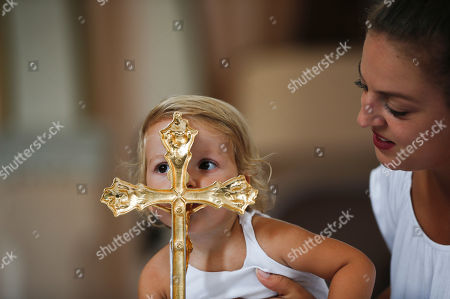 Anarita Mihilli, is being held by her mother as she kisses the gold plated cross in the church of the Black Madonna, during the feast of Assumption in the village of Letnica, Kosovo, . Thousands of pilgrims gathered in southeastern Kosovo in the small Roman Catholic community where Mother Teresa is believed to have heard her calling to become a nun