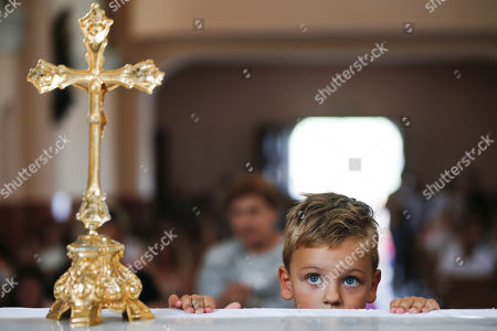 A three year old Justinian Mihilli, looks on near the gold plated cross in the church of the Black Madonna, during the feast of Assumption in the village of Letnica, Kosovo, . Thousands of pilgrims gathered in southeastern Kosovo in the small Roman Catholic community where Mother Teresa is believed to have heard her calling to become a nun