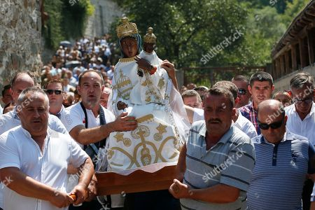 Pilgrims carry the wooden icon of the Black Madonna, during the feast of Assumption in the village of Letnica, Kosovo, . Thousands of pilgrims gather in southeastern Kosovo in the small Roman Catholic community where Mother Teresa is believed to have heard her calling to become a nun