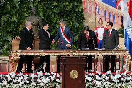 """Paraguay's new President Mario Abdo Benitez, center, shakes hands with his predecessor Horacio Cartes, as Supreme Court president Judge Raul Torres Kimser, left, New Vice President Hugo Velazquez Marito, second right, and is seen during inauguration ceremony at """"Lopez Palace"""" in Asuncion, Paraguay, . Abdo Benitez is the 50th Paraguay's President"""
