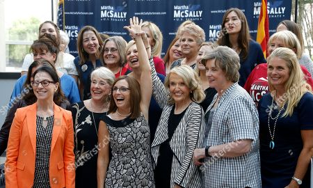 Rep. Martha McSally, R-Ariz., third from left, laughs as she gets her arm raised by former Arizona Republican Gov. Jan Brewer, third from right, as they pose for a photograph with members of the Women's Coalition after a news conference at a campaign event for McSally's U.S. Senate primary race, in Phoenix. McSally, Kelli Ward and former Maricopa County Sheriff Joe Arpaio are vying for the Republican nomination, but there are no plans currently for a televised debate for the Republican candidates, on the Democratic side, Rep. Kyrsten Sinema and activist Deedra Abboud haven't had a televised debate either
