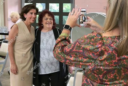 Rhode Island Gov. Gina Raimondo, left, poses for a photo with a constituent at the Pilgrim Senior Center in Warwick, R.I. Former Secretary of State Matt Brown is challenging Raimondo in the Sept. 12 Democratic primary as she seeks a second term