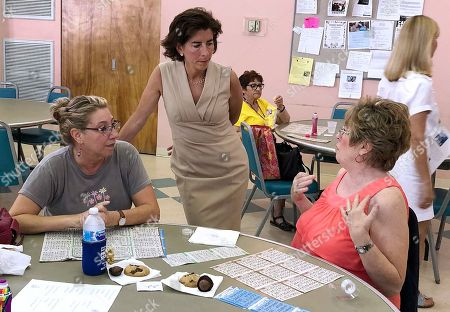 Rhode Island Gov. Gina Raimondo, center, speaks with Lisa McGovern, left, and Betty Toye at the Pilgrim Senior Center in Warwick, R.I. Former Secretary of State Matt Brown is challenging Raimondo in the Sept. 12 Democratic primary as she seeks a second term