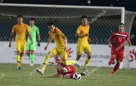 Shihao Wei, Mohammad Almarmour. China's Shihao Wei, center,battles for the Syria's Mohammad Almarmour during their men's soccer match between China and Syria at the 18th Asian Games at Si Jalak Harupat Stadium in Bandung, Indonesia
