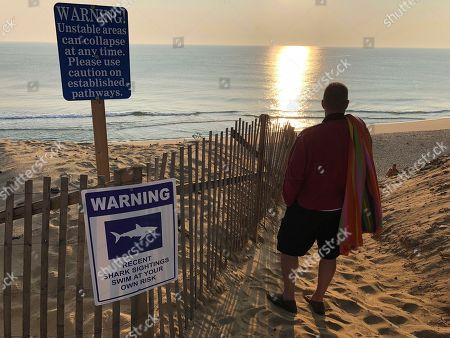 Steve McFadden, 49, of Plattsburgh, N.Y. gazes at Long Nook Beach in Truro, Mass., on . Authorities closed the Cape Cod beach to swimmers after a man was attacked by a shark on Wednesday, the first attack on a person in Massachusetts since 2012. The unidentified victim survived the attack and was airlifted to a Boston hospital