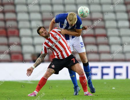 Frederik Nielsen of Sheffield Wednesday gets to the ball ahead of Chris Maguire of Sunderland