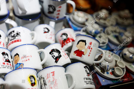 Souvenir cups featuring caricatures of Chinese President Xi Jinping and former leader Mao Zedong are seen in a shop in Hong Ya Dong or Red Cliff Cave, a popular tourist spot in Chongqing, China, 16 August 2018. Chongqing is a major city in the southwest of China and is one of the top tourism cities in the country with thousands of visitors thronging its popular tourists sites everyday.