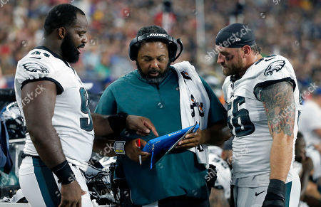 Philadelphia Eagles defensive line coach Chris Wilson, center, confers with defensive ends Fletcher Cox, left, and Chris Long, right, on the sideline during the first half of a preseason NFL football game against the New England Patriots, in Foxborough, Mass