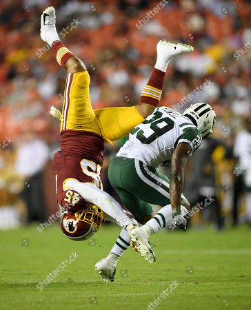 Washington Redskins linebacker Pete Robertson (45) is upended next to New York Jets running back Bilal Powell (29) during the first half of a preseason NFL football game, in Landover, Md