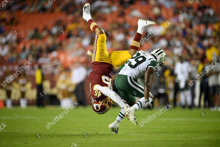 Washington Redskins linebacker Pete Robertson (45) is upended against New York Jets running back Bilal Powell (29) during the first half of a preseason NFL football game, in Landover, Md
