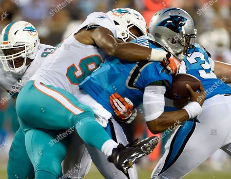 Carolina Panthers' Cam Newton, right, is sacked by Miami Dolphins' Robert Quinn, left, in the first half of a preseason NFL football game in Charlotte, N.C