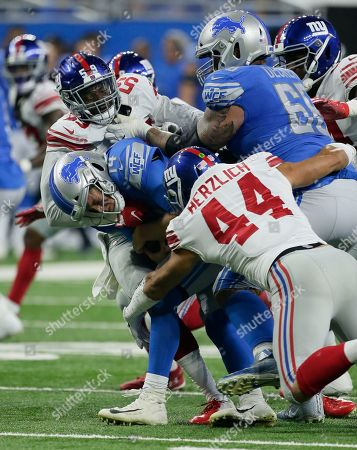 Stock Photo of Detroit Lions offensive tackle Taylor Decker (68) can't stop New York Giants linebackers Lorenzo Carter (59) and Mark Herzlich (44) from sacking Detroit quarterback Jake Rudock (14) during the first half of a preseason NFL football game, in Detroit
