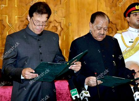 In this photo released by Pakistan's Press Information Department, Pakistani President Mamnoon Hussain, center, administers oath to newly-elected Prime Minister Imran Khan, left, at Presidential Palace in Islamabad, Pakistan, . Pakistan's cricket star-turned-politician Imran Khan was sworn in as prime minister on Saturday despite protests by opposition parties, which accuse the security services of intervening on his behalf in last month's elections