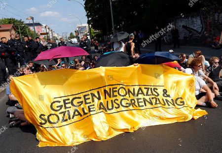 Counter-demonstrators sit on the pavement with a banner reading ' Against neonazis & social exclusion' against a demonstration commemorating the death anniversary Rudolf Hess in Berlin, Germany, 18 August 2018. Hess died on 17 August 1987 after committing suicide in the Spandau Prison, where he served his life sentence. Hess was one of the most prominent Nazi leaders and appointed Deputy Fuehrer by German dictator Adolf Hitler in 1933.