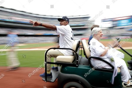 Stock Picture of Former New York Yankees third base coach Willie Randolph gesture while riding on a cart with Soot Zimmer, right, wife of the late Yankees coach Don Zimmer, after an on-field ceremony honoring the team's 1998 World Series championship prior to a baseball game between the New York Yankees and the Toronto Blue Jays, in New York
