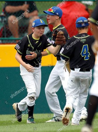 Australia's right fielder Matthew White (10) shows the ball to the umpire and is congratulated by teammates Oscar Hyde and Tyler Salmon-Patrick after making a diving catch against Puerto Rico to end the fifth inning of an elimination baseball game in International pool play at the Little League World Series tournament in South Williamsport, Pa., . Puerto Rico won the game 6-0 eliminating Australia