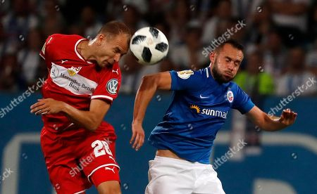 Pascal Breier (R) of Rostock and Holger Badstuber of Stuttgart in action during the German DFB Cup first round soccer match between F.C. Hansa Rostock and VfB Stuttgart in Rostock, Germany, 18 August 2018.  (ATTENTION: The DFB prohibits the utilisation and publication of sequential pictures on the internet and other online media during the match (including half-time). ATTENTION: BLOCKING PERIOD! The DFB permits the further utilisation and publication of the pictures for mobile services (especially MMS) and for DVB-H and DMB only after the end of the match.)