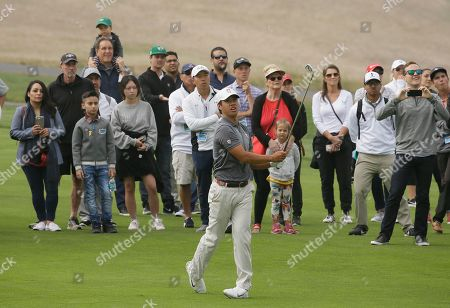 Isaiah Salinda follows his shot from the 14th fairway of the Pebble Beach Golf Links during the semifinal round of the USGA Amateur Golf Championship, in Pebble Beach, Calif. In the background is broadcaster Jim Nantz with a child on his shoulders
