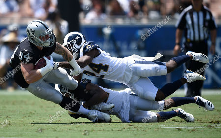 Stock Photo of Oakland Raiders tight end Paul Butler, left, is tackled by Los Angeles Rams cornerback Blake Countess (24) and cornerback Troy Hill during the first half in an NFL preseason football game, in Los Angeles