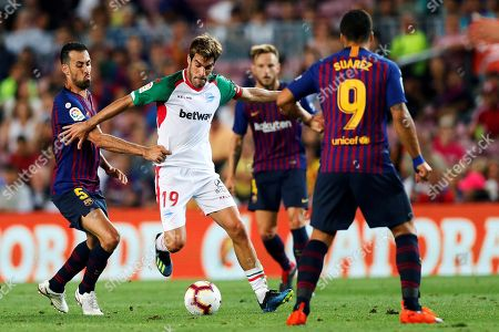 Manuel Alejandro García (C) of Alaves in action against Barcelona's Sergio Busquets (L) during the Spanish Primera Division soccer match between Barcelona FC and Deportivo Alaves, at the Camp Nou Stadium, in Barcelona, Spain, 18 August 2018.