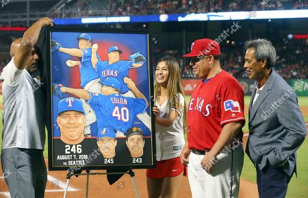 Artist Vernon Wells unveils a painting that was presented to Texas Rangers' Bartolo Colon for becoming the winningest Latin American pitcher, surpassing Dennis Martinez, right, before a baseball game between the Los Angeles Angels and the Rangers, in Arlington, Texas