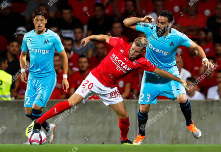 Renaud Ripart (C) of Nimes in action against Marseille players Hiroki Sakai (L) and Adil Rami (R) during the French Ligue 1 soccer match between Nimes Olympique and Olympique Marseille in Nimes, southern France, 19 August 2018.