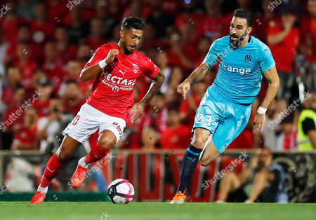 Adil Rami (R) of Marseille in action against Denis Bouanga (L) of Nimes during the French Ligue 1 soccer match between Nimes Olympique and Olympique Marseille in Nimes, southern France, 19 August 2018.