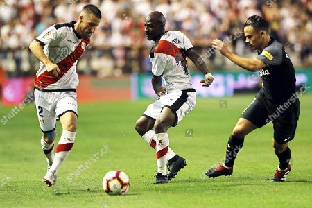 Sevilla's Roque Mesa (R) in action against Rayo Vallecano players Tito (L) and Gael Kakuta (C) during the Spanish Primera Division soccer match between Rayo Vallecano and Sevilla FC at the Vallecas stadium in Madrid, Spain, 19 August 2018.